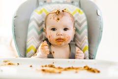 Маленький младенец есть ее обедающий и делая беспорядок стоковое изображение