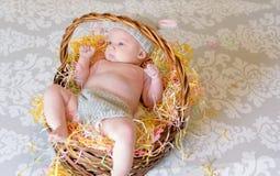 Маленький младенец кладя в корзину пасхи с обмундированием зайчика Стоковое фото RF