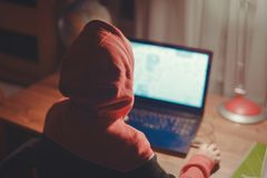 Маленький ребенк gamer в клобуке играя массовую предназначенную для многих игроков игру онлайн на ноутбуке стоковые фотографии rf