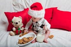 Маленький ребенок в красной крышке ест печенья и молоко Фотография рождества младенца в красной крышке Праздники и рождество Ново стоковое изображение rf