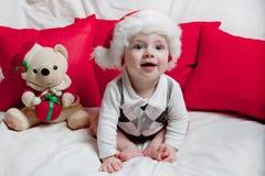 Маленький ребенок в красной крышке ест печенья и молоко Фотография рождества младенца в красной крышке Праздники и рождество Ново стоковая фотография