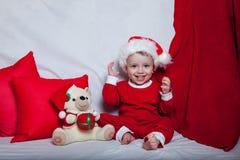 Маленький ребенок в красной крышке ест печенья и молоко Фотография рождества младенца в красной крышке Праздники и рождество Ново стоковые изображения rf