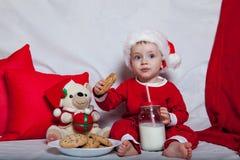 Маленький ребенок в красной крышке ест печенья и молоко Фотография рождества младенца в красной крышке Праздники и рождество Ново стоковые фото