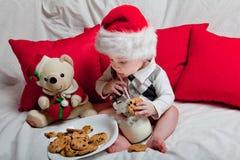 Маленький ребенок в красной крышке ест печенья и молоко Pho рождества стоковая фотография rf