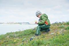 Маленький ребенок в куртке и шляпе собирая весну цветет на зеленом наклоне против фона моря Стоковые Изображения RF