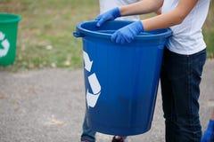 Маленький ребенок держа в руках голубой рециркулируя ящик на запачканной естественной предпосылке Концепция загрязнения экологичн Стоковая Фотография RF
