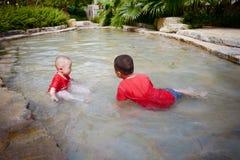 Маленький ребенок играя снаружи в потоке стоковое фото rf