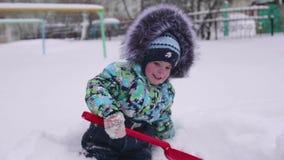 Маленький ребенок играя с снегом в парке зимы Ребенок держа лопаткоулавливатель, серии снега в парке Потеха и игры в акции видеоматериалы
