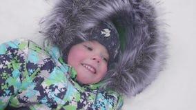 Маленький ребенок играя с снегом в парке зимы Лежа и усмехаясь младенец на белом пушистом снеге Потеха и игры в свежей видеоматериал
