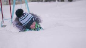 Маленький ребенок играя с снегом в парке зимы Лежа и усмехаясь младенец на белом пушистом снеге Потеха и игры в свежей сток-видео