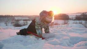 Маленький ребенок играя с снегом в парке зимы Солнечный день ` s зимы Потеха и игры в свежем воздухе видеоматериал