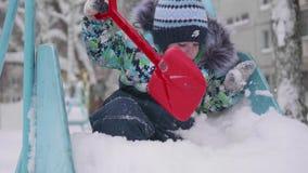 Маленький ребенок играя с снегом в парке зимы Солнечный день ` s зимы Потеха и игры в свежем воздухе акции видеоматериалы