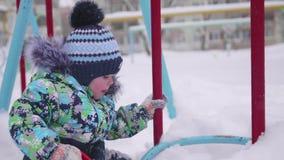 Маленький ребенок играя с снегом в парке зимы Солнечный день ` s зимы Потеха и игры в свежем воздухе сток-видео
