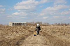 Маленький ребенок идет на дорогу через поле к незаконченной строя игрушке автомобиля колес стоковая фотография rf