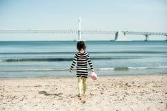 Маленький ребенок идя в песок моря раннего лета, Корея Gwangalli Стоковое фото RF