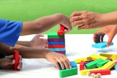 Маленький ребенок и семья играя деревянные цвета для того чтобы преградить игру в учить деятельности для того чтобы начать IQ дет стоковое фото