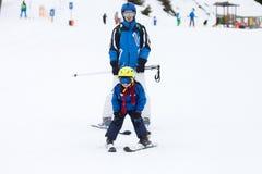 Маленький ребенок, катаясь на лыжах на наклоне снега в лыжный курорт в Австрии Стоковые Фотографии RF