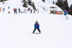 Маленький ребенок, катаясь на лыжах на наклоне снега в лыжный курорт в Австрии Стоковые Изображения