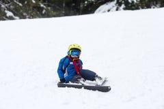 Маленький ребенок, катаясь на лыжах на наклоне снега в лыжный курорт в Австрии Стоковая Фотография RF