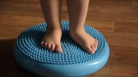 Маленький ребенок массажирует его ноги пока стоящ на половике сток-видео