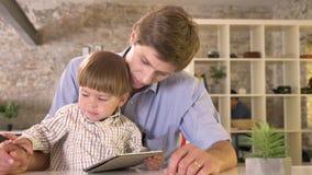 Маленький ребенок надоел его отцом, принимая руку ` s папы далеко от таблетки, сидя в современном офисе сток-видео