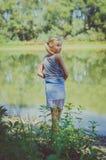 Маленький ребенок рекой смотря назад Стоковая Фотография RF