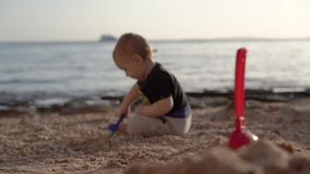 Маленький ребенок сидит на пляже и играет с грабл в замедленном движении - из фокуса акции видеоматериалы