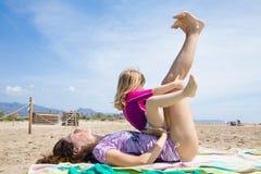 Маленький ребенок сидя на женщине играя с ее ногами на пляже стоковое изображение rf