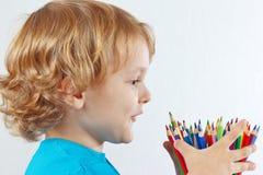 Маленький ребенок смотрит на карандашах цвета на белой предпосылке Стоковая Фотография RF