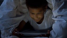 Маленький ребенок смотря таблетку секретно на ноче, предусматриванной с головой в одеяле стоковое фото