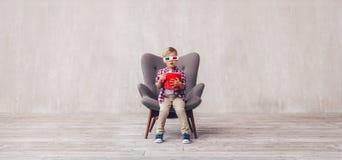 Маленький ребенок с попкорном в стеклах 3d стоковое изображение rf