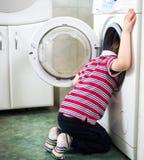 Маленький ребёнок опасно кладя его головку в барабанчик стиральной машины Стоковые Фотографии RF
