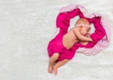Маленький ребёнок сладостно сон в розовых шарфах стоковое фото