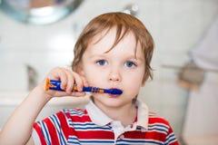 Маленький ребёнок чистя его зубы щеткой в ванной комнате Стоковые Фотографии RF