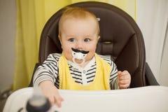 Маленький смешной мальчик сидя в стуле для подавать с ребяческой ниппелью в форме усика Стоковая Фотография RF
