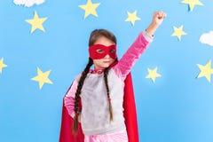 Маленький супергерой детских игр Оягнитесь на предпосылке яркой голубой стены Стоковое Фото