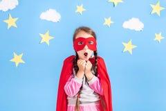 Маленький супергерой детских игр Оягнитесь на предпосылке яркой голубой стены с белыми облаками и звездами Концепция силы девушки Стоковые Фотографии RF