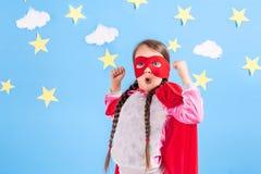 Маленький супергерой детских игр Оягнитесь на предпосылке яркой голубой стены с белыми облаками и звездами Концепция силы девушки Стоковые Изображения RF