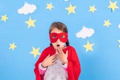 Маленький супергерой детских игр Оягнитесь на предпосылке яркой голубой стены с белыми облаками и звездами Концепция силы девушки Стоковая Фотография