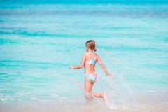 Маленький счастливый брызгать девушки Оягнитесь ход к воде бирюзы готовой для того чтобы поплавать Стоковое Изображение