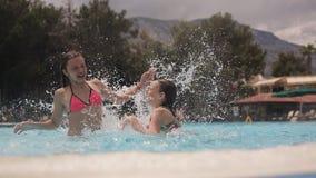 Маленький счастливый делать девушек брызгают и смеяться над в бассейне видеоматериал