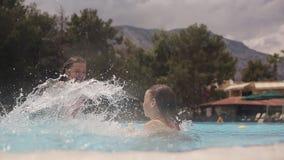 Маленький счастливый делать девушек брызгают и смеяться над в бассейне акции видеоматериалы