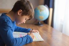 Маленький умный школьник разрешая домашнюю работу примеров математики Стоковые Изображения