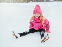 Маленький усмехаясь конек девушки и упал на лед в розовой носке напольно Стоковое Фото