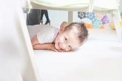 Маленький усмехаясь мальчик лежит на поле дома Стоковые Изображения