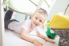 Маленький усмехаясь мальчик лежит на поле дома Стоковые Изображения RF