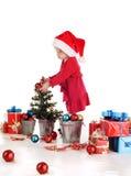Маленький хелпер santa украшая дерево Стоковые Изображения