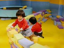 2 маленьких азиатских ребенка, сестры, штабелируя вверх по кирпичам здания пены/преграждают совместно на крытой спортивной площад стоковые изображения rf