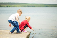 2 маленьких белокурых дет, мальчик и девушка, сидя на пристани на lak Стоковое фото RF