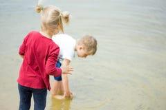 2 маленьких белокурых дет, мальчик и девушка, стойка на береге озера Стоковое фото RF